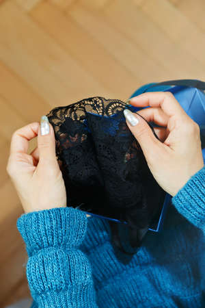 Young adult woman in blue dress unpacking black lacy lingerie item from a box on her knees. Holiday gift presenting concept, suitable for Saint Valentine day. First person top view, vertical capture.
