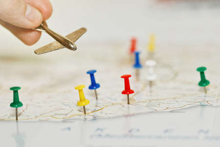 Person holding a tiny aircraft toy above the map with colored pins highlighting places of visit and tourism interest on the travel route. Journey planning concept. Close-up capture, selective focus.