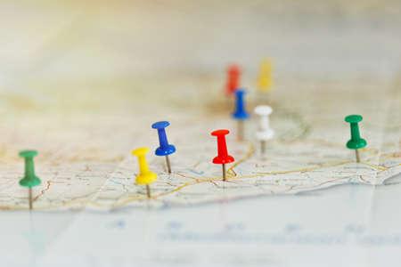 Kaart van een kust met hoogtepunten van de route en interessante plaatsen gemarkeerd met gekleurde spelden. Vakanties voorbereidingen idee, routeplanning concept. Close-up opname, selectieve focus, onherkenbare namen.
