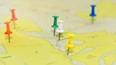 Geographical map with pushpins symbolizing main points of travel route, country highlights and places of interest. Trip planning concept. Close-up capture, selective focus, unrecognizable names.