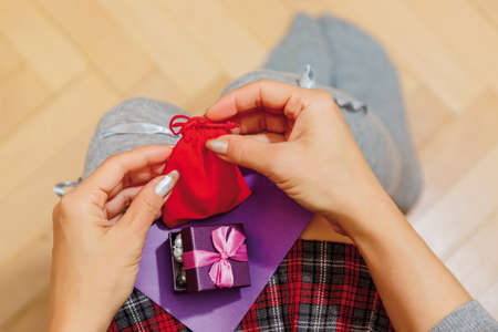 Person in schoolgirl checkered skirt and high warmer socks with some little gifts presented on holiday probably Saint Valentine day and a congratulation card on her knees. First person top view.