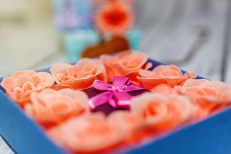 Ready to present gift idea - tiny box surrounded by many pink rose blossoms packed in bigger box. Valentine day or wedding gift idea. Celebration prepare concept. Close-up capture, selective focus.