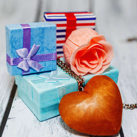 Some gift boxes collected in a pile with a pink rose blossom and wooden heart pendant. Romantic gift, probably for Valentine day. engagement or wedding concept. Close-up capture, selective focus.