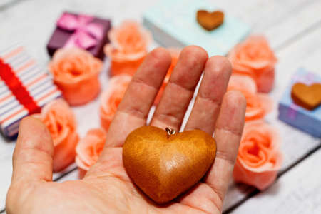 Male person holding vintage wooden heart pendant. Rose blossoms, gift boxes and other romantic symbols on background. Engagement, valentine day or marriage offer concept. Selective focus, close-up. Reklamní fotografie