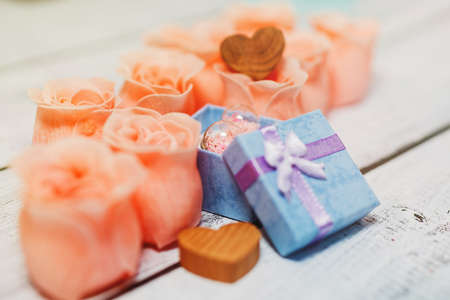 Tiny box with a gift inside surrounded by romantic love symbols - pink rose blossoms and wooden hearts. Ready to present Valentine day, wedding or engagement gift concept. Close-up, selective focus. Reklamní fotografie