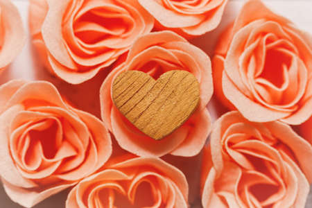 Wooden handmade heart with rough texture, symbol of romantic love, lie on delicate pink rose blossoms. Valentine day, wedding or engagement concept. Close-up high angle capture, selective focus.