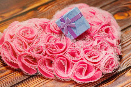 Tiny gift box with silk ribbon lie on rose heart shaped decoration made of man-made synthetic rose blossoms. Valentine day or engagement present idea, romantic love concept. Selective focus.