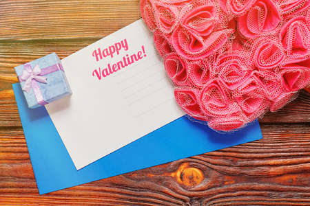 St Valentine day greeting card and an envelope with romantic symbols nearby - tiny gift box and heart-shaped ornament made of man-made pink rose blossoms. Top view capture, light leak effect.