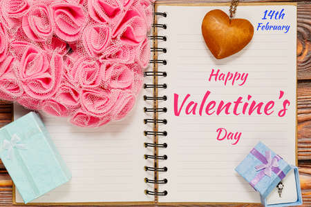 Opened calendar notepad with date - 14 of February and Valentine day congratulations message and romantic symbols around - gift boxes with jewelry item, heart shaped wooden pendant, etc. Top view.