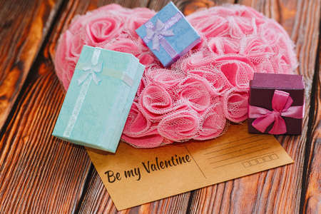 Valentine day celebration concept - vintage postcard with congratulations message, heart shaped ornament made of man-made pink roses and tiny gift boxes with ribbons and bows. Selective focus.