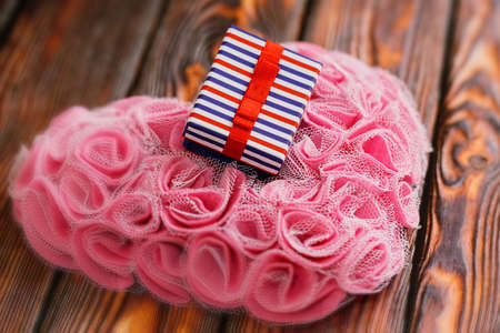 Striped ready to present gift box on romantic heart shaped ornament made of man-made pink rose blossoms lie on wooden table. Valentine day surprise present idea. Selective focus, close-up capture. Standard-Bild