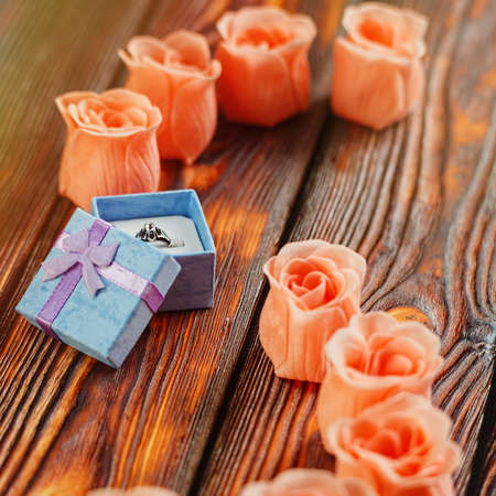 Tiny gift box with a silver ring with jewel or gem on wooden table surrounded by few pink rose blossoms. Engagement or marriage present concept, romantic idea Close-up capture, selective focus.