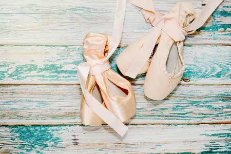 Ballet shoes with pointing toe with ribbons, mandatory part of dancer outfit, lie on rough painted wooden background - theater stage. After the show, behind scenes concept. Top view, place for text.