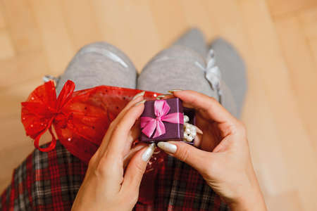 Teenage female person in schoolgirl skirt unpacking gift - pearl bracelet in tiny box with bow holding it on her knees. Saint Valentine day or birthday present concept. First person view.