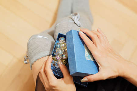 White young adult woman opens a gift box on her knees with a jewelry decorative item. Present for a holiday concept - St Valentine day, birthday or New Year. First person top view. Selective focus.