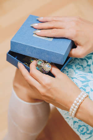 Young adult white woman in fancy dress opening a gift box with decorative item. Standard-Bild