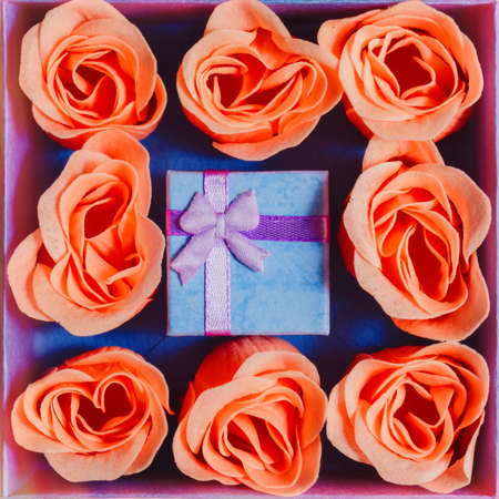 Tiny gift box with a bow in bigger one surrounded by pink rose blossoms - surprise present decoration design concept, idea for Valentine Day or engagement. Top view, square capture.