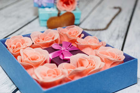 Gift package idea - tiny box with pink rose blossoms in bigger one ready to present and some more accessories on the background. Romantic surprise concept. Close-up capture, selective focus.