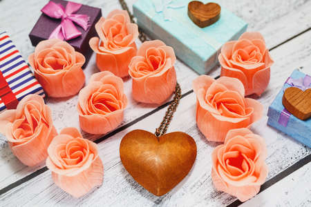 Love symbols on the wooden background - heart shaped pendant, pink rose blossoms and gift boxes. Romantic celebrations concept for Valentine Day, wedding or engagement. Close-up capture. Reklamní fotografie