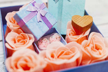 Romantic surprise design concept - box with pink rose blossoms and heart shaped figurines, traditional symbols of love, and tiny gifts inside. Close-up macro capture, selective focus. Standard-Bild