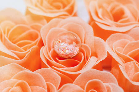 Few pink rose blossoms, traditional love symbol, and a decorative item - glass ball with tiny stars - on one of them. Romantic concept, gift packing idea. Extreme close-up capture, selective focus. Reklamní fotografie