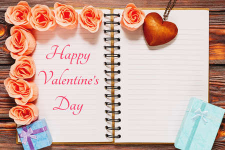 Opened diary with Valentine Day lettering, with copyspace, decorated by traditional love and romance symbols - pink rose blossoms, gift boxes with bows, heart shaped pendant. Top view, place for text.
