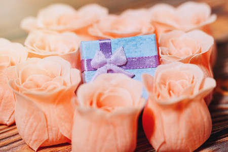 Romantic present concept. Tiny gift box hided among rose blossoms, traditional symbols of love. Valentine Day, engagement or other romantic event concept. Extreme close-up capture, selective focus.