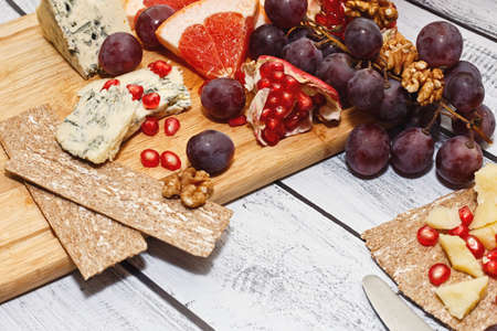 Light european cuisine way snack idea - ripped blue cheese sliced on cutting board served with assortment of fresh fruits, walnuts and wholegrain rye crackers. Close-up capture, selective focus. Reklamní fotografie
