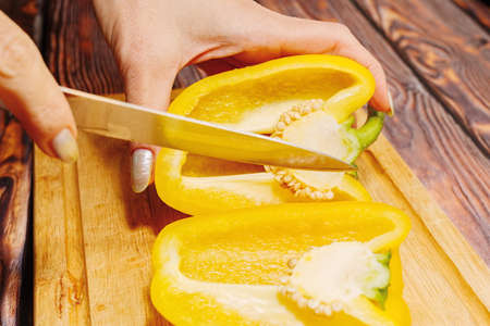 Young adult woman slicing natural bell pepper on a cutting board on wooden kitchen table. Home everyday cooking concept. Close-up capture, selective focus. Reklamní fotografie