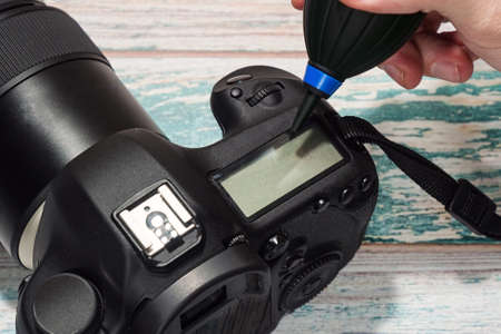 Removing dust from DSLR camera body with an air pump cleaner - part of necessary proffesional service for photographic equipment. Close-up capture, selective focus. Standard-Bild