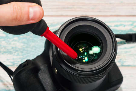 Dust removing from a digital SLR camera lens with an air pump. Taking care of proffesional photographer equipment concept, camera service idea. Close-up capture, selective focus.