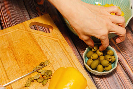 Woman cutting green olives and yellow bell pepper for salad cooking on cutting board on wooden kitchen table. Home culinary concept.