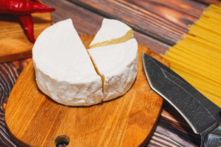 Gourmet brie or camembert cheese slice on a cutting board and ready for cooking on a wooden kitchen table. Pasta and red hot chili peppers lie nearby. Close-up capture, selective focus.
