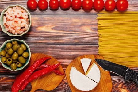 Assortment of raw cooking ingredients on a wooden kitchen table - spaghetti pasta, cherry tomatoes, shrimps, green olives, hot chili pepper and soft gourmet cheese. Top view, place for text.