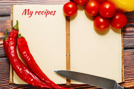 Opened vintage recipes book with empty pages with hot spicy chili pepper and tiny cherry tomatoes on it. Wooden table on a background. Home cuisine concept. Top view, place for text.