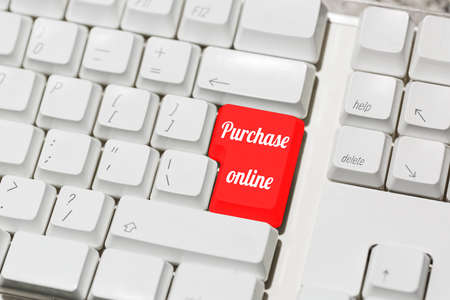 Computer keyboard with special online purchasing red key instead of enter. Online shopping payment concept. Purchasing with internet in one touch idea. Close-up capture, selective focus.