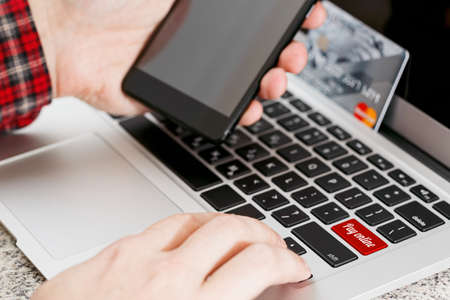 Person holding a smartphone preparing for online payment. Credit card on laptop in the background. Waiting for disposable password during online shopping concept. Close-up capture, selective focus.