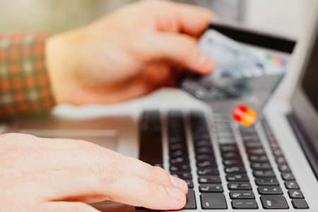 Male person makes an online payment or purchase, holding credit cards in his hand and preparing to pay via laptop. Safe online banking transactions concept. Close-up capture, selective focus.