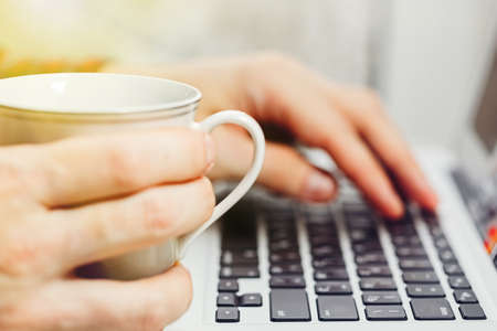 Male person holding a cup of coffee and working on a laptop keyboard. Tranquil and cozy working process concept. Close-up capture, selective focus.