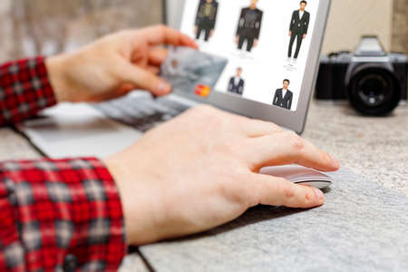 Male person in checkered shirt doing online apparel shopping and ready to make payment via credit card. Online clothes store web page opened on laptop screen. Close-up capture, selective focus. Standard-Bild