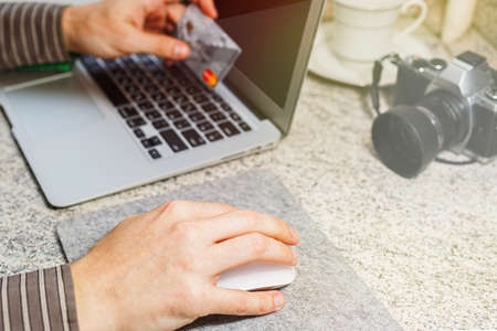 Man in shirt prepares for online payment or other banking transaction via internet. Credit card in one hand, computer mouse in other and an opened laptop. Close-up capture, selective focus.