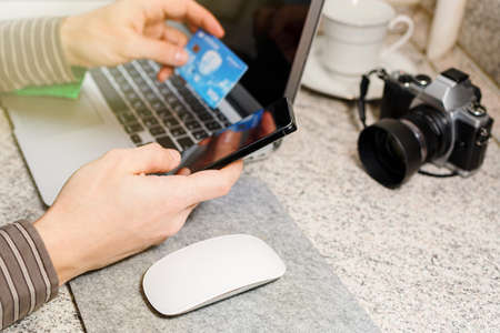 Male person in striped shirt with laptop and smartphone making an online payment or purchase with his credit card. Waiting for disposal password, safe transaction technology. Selective focus.