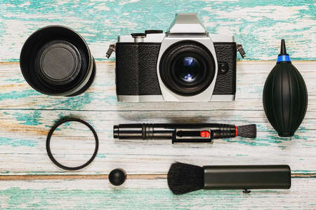 Vintage style camera and lens with cleaning kit - air pump, cleaning pen, brush and lens protective filter on rough painted wooden background. Taking care of photographer equipment concept. Top view. Reklamní fotografie