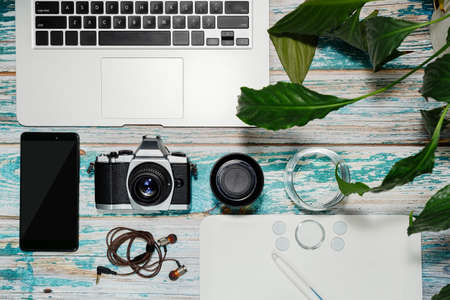 Photographer equipment - laptop, vintage style DSLR camera, lens, graphics tablet and smartphone with some accessories collected on rough painted loft style table. Blogger workspace concept. Top view.