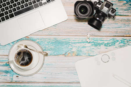 Vintage loft style wooden table with laptop, vintage camera with lenses, graphics tablet and a cup of coffee. Freelance photographer, blogger or designer workspace concept. Top view.