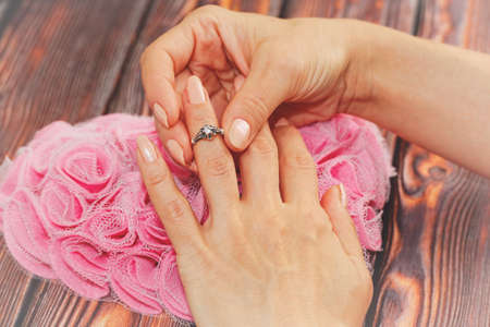 Young adult female person puts on a silver ring with a jewel. Heart shaped decoration on the background, love and romance symbol. Engagement or wedding romantic concept. Close-up capture.