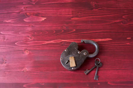 lock: Old Fashioned Lock and Keys on a Red Wooden Background