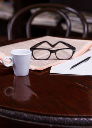 paper and pen: Newspapers and coffee cup, reading glasses, pen and striped paper.
