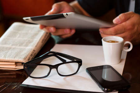 Newspapers and coffee cup, reading glasses, striped paper, hands holding tablet, cell phone.