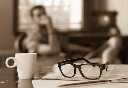 Newspapers and coffee cup, reading glasses, pen and striped paper. photo